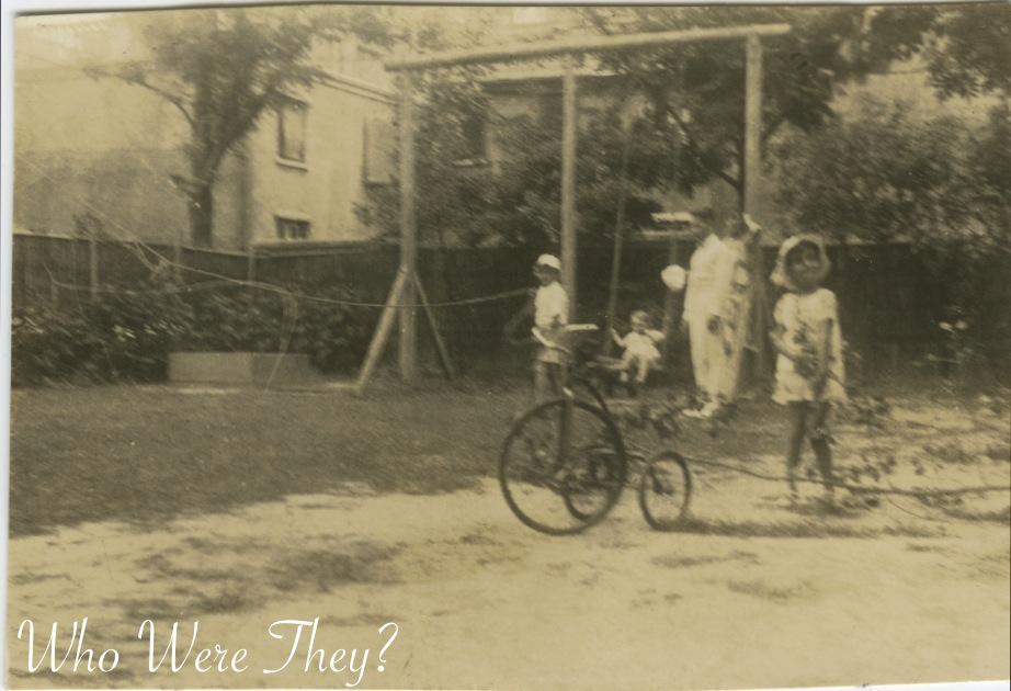 Three children and an adult in the backyard. I love the old style tricycle ...