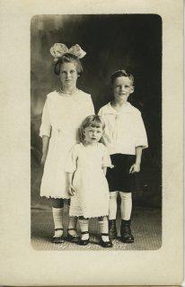 Three children, one big bow